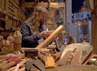 Gary Waidson demonstrating Viking age leather working techniques in the longhouse at Borg